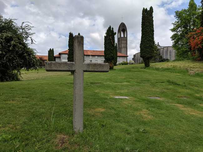 View of a green hillside up to a church. In the foreground is a plain cross in a graveyard.