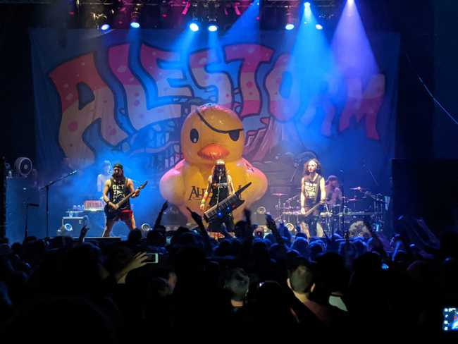 Heavy metal band performing with flood lights and a giant inflated rubber duck.